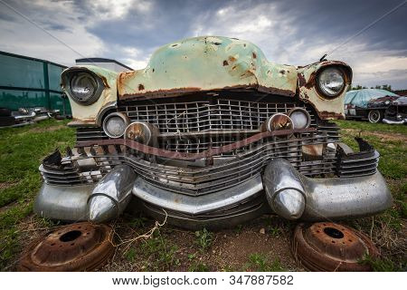 Close Up On A Rusty Old Classic Car Front, Abandoned With Broken Parts In The Junkyard