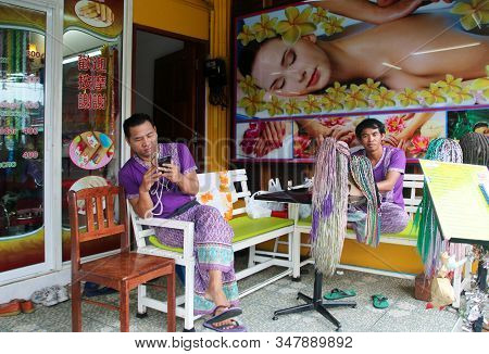 Patong, Phuket, Thailand - January 30, 2020: Unidentified Thai Masseurs Seat In Front Of Their Massa