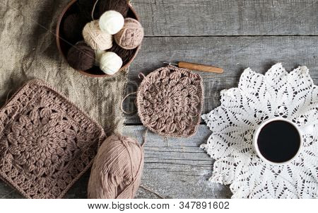 Crochet Process From Soft Woolen Yarn Of Brown Color. Woolen Yarn On A Wooden Background.