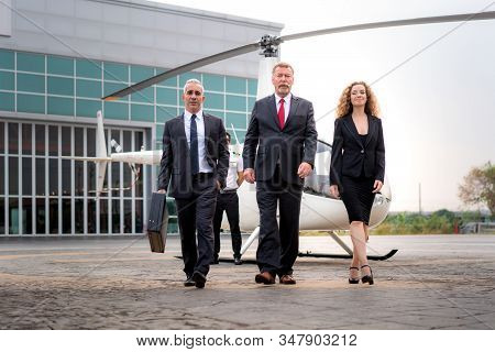 Three Businessman And Businesswoman Manager With Briefcase Walking From Helicopter When He Arrive De