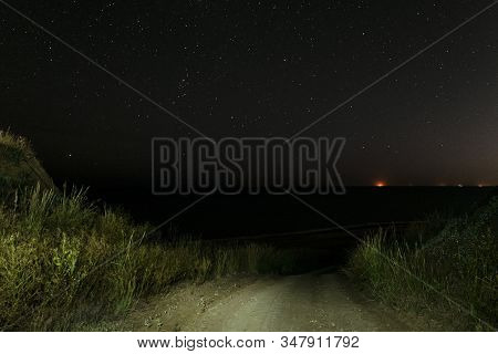 Descent Of A Dirt Road From A Hill To The Night Sea. Sea Coast At Night. Starry Nightscape Over The