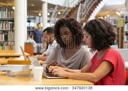 Two Thoughtful Women Talking And Typing On Laptop. Concentrated Ladies Talking While Sitting At Tabl