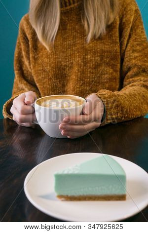 Woman In Terracotta Sweater Headless And Hands With Latte. Turquoise Background, Brown Wooden Table.
