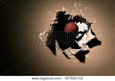 A Creepy Scary Vampire Clown With A Red Nose Shows His Fangs Through Torn Cardboard. Halloween Theme