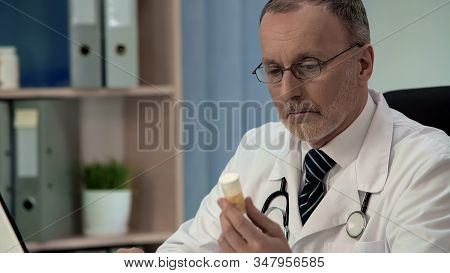 Doubtful Doctor Looking At Pills, Counterfeit Poor Quality Medicines, Placebo