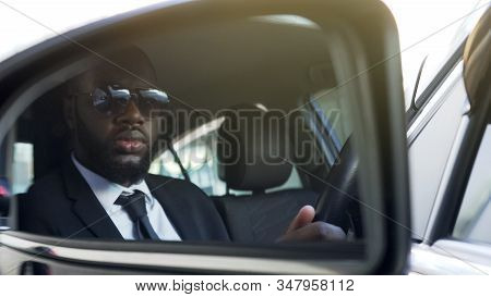 Black Man In Sunglasses Driving Car, Looking In Side-view Mirror, Bodyguard