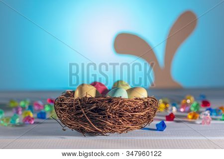 Easter Nest, Hidden Eggs By A Hare.  Easter Bunny On A Blurry Background. Spring Religious Holiday.