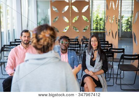 Back View Of Woman With Plait Standing In Front Of Colleagues. Coworkers Sitting And Listening Speak