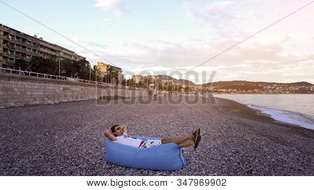Young Man Lying Down On Hangout Sofa To Enjoy Rest On Sea Beach, Summer Relax