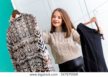 Cute Brunette Girl Choosing Her Outfit, Holding Two Dresses On Wooden Hangers.