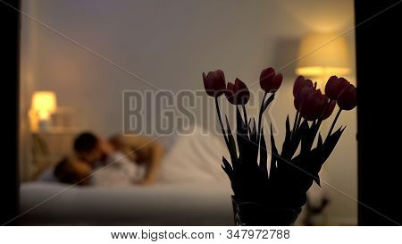 Couple Making Love After Romantic Date, Flowers Standing On Table In Bedroom