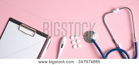 Medical Equipment And Tools On Pink Background. Top View Doctors Desk Table With Medical Clipboard,