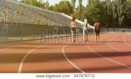 Three Sportive Girls Walking On Stadium Track After Exercising, Team Relaxing