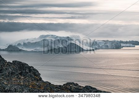 Arctic Nature Landscape With Icebergs In Greenland Icefjord. During Midnight When Sunset And Sunrise