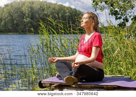 Young pregnant woman wearing sporty dress doing yoga exercise sitting in lotus position on a wooden pier at a forest lake meditating. Fitness and healthy lifestyle during pregnancy concept