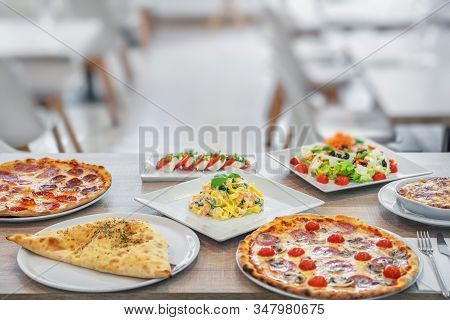 A Group Of Italian Dishes In The Restaurant For Lunch. Pizza, Lasagne, Salad, Puri, Feta. Restaurant
