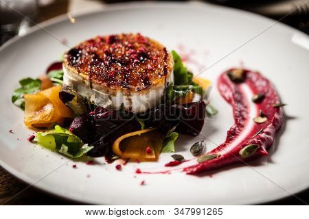 Grilled Goat Cheese Salad Served On A Plate In Restaurant