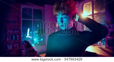 Thinking. Cinematic Portrait Of Stylish Redhair Man In Neon Lighted Interior. Toned Like Cinema Effe