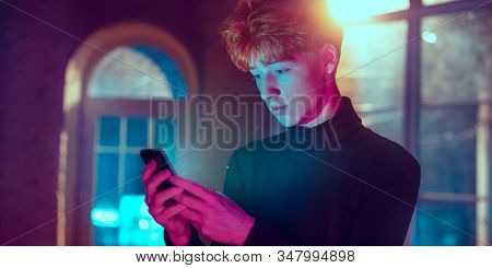 Calm, Serious. Cinematic Portrait Of Stylish Redhair Man In Neon Lighted Interior. Toned Like Cinema