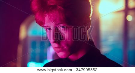 Close Up. Hard Looking. Cinematic Portrait Of Redhair Young Man In Neon Lighted Interior. Toned Like