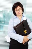 Sloppy businesswoman with briefcase looking at camera poster