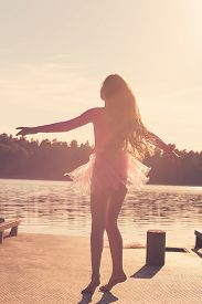 Beautiful Teen Girl With Long Flowing Curly Hair Is Dancing  In The Wind Against The Background Of T