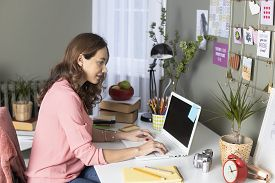 Woman Working From Home. Freelance Working At Home. She Is Designing Her Laptop On The Desk