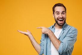 Excited Young Bearded Man In Casual Blue Shirt Posing Isolated On Yellow Orange Background, Studio P