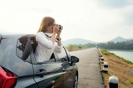 Young Asian Woman Tourist Taking Photo In Car With Camera Driving On Road Trip Travel Vacation. Girl