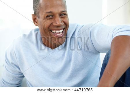 Image of young African man looking at camera and laughing