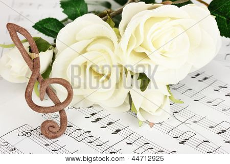 Treble clef and roses on musical background