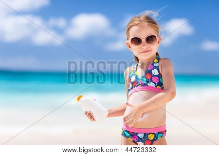 Adorable little girl at tropical beach applying sunblock cream poster