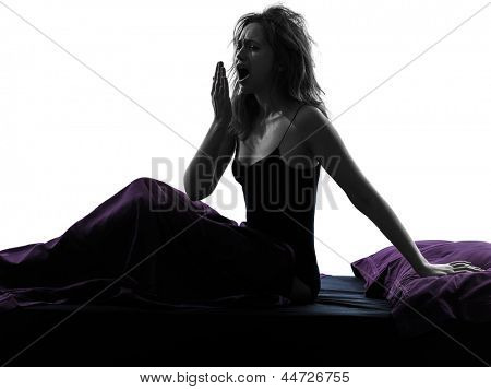 one woman yawning sitting on bed silhouette studio on white background
