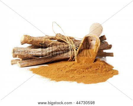 Pile of ground licorice with wooden shovel and licorice roots (glycyrrhiza glabra)
