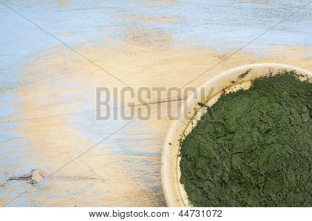 small bowl of Hawaiian spirulina powder against wood background