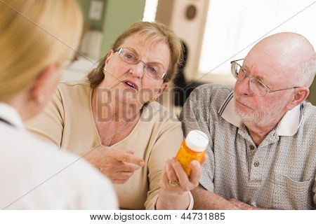 Doctor or Nurse Explaining Prescription Medicine to Attentive Senior Couple. poster