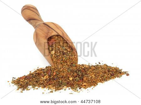 Harissa spice powder in an olive wood scoop over white background.