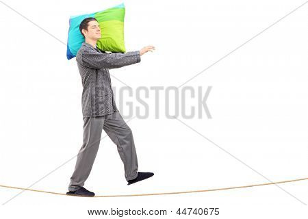Full length portrait of a man sleepwalking on a rope, isolated on white background