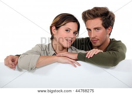 Couple leaning against a blank poster