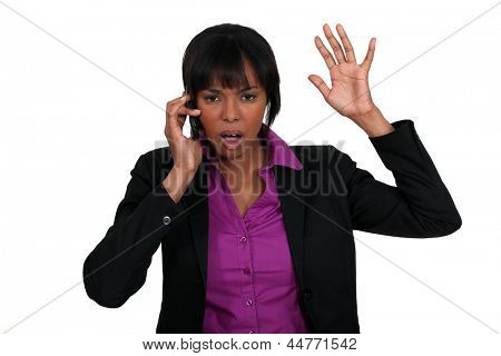 A black businesswoman angry over the phone.