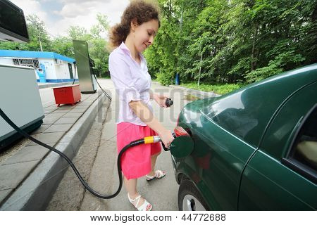 Young beautiful smiling woman fills petrol car on sunny summer day.