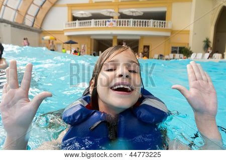 Happy girl in lifejacket in the water park with his hands up.