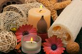 Spa concept with aromatic candles, herbs, beautiful daisies, massage oil and loofah poster