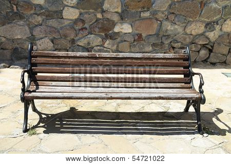 old bench on the background of a stone wall