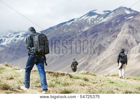 Three tourist traveller hiker walking in india Himalayas mountains