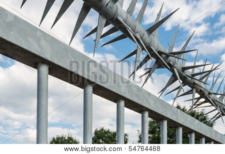 Detail of a zinc plated steel fence with sharp spikes. poster