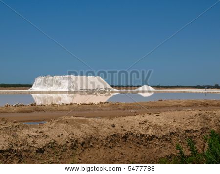 Salt Lagoon With Large Pile Of Salt Reflected In Water.