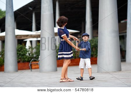 Young mother and her son playing outdoors in city
