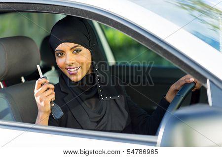 happy arabian woman holding car key inside new vehicle