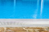 edge of the swimming pool overflow with blue seawater poster